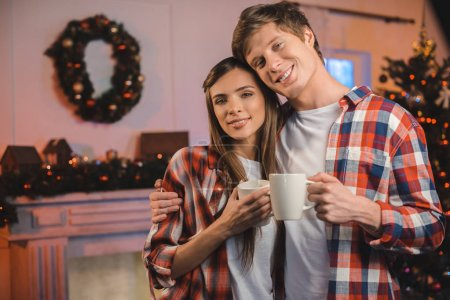 Couple with cups of hot drinks