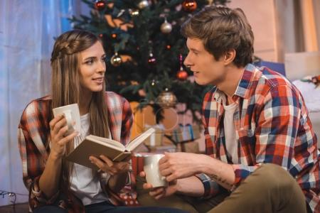 couple with cups of hot drinks and book