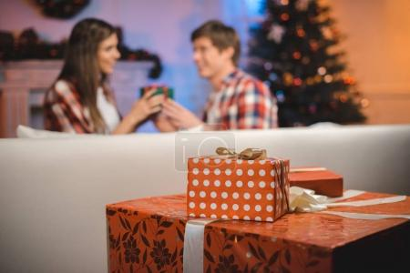 Photo for Selective focus of wrapped christmas gifts and young couple in decorated room at home - Royalty Free Image