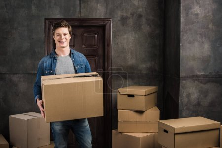 Photo for Portrait of cheerful man with cardboard box in hands moving at new home - Royalty Free Image