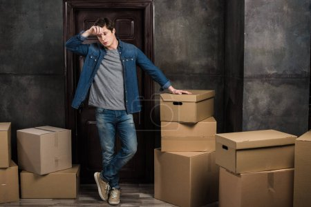 Photo for Tired young man standing in room full of cardboard boxes at new home - Royalty Free Image