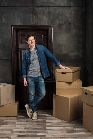 Photo for Smiling young man looking away while standing in room full of cardboard boxes at new home - Royalty Free Image