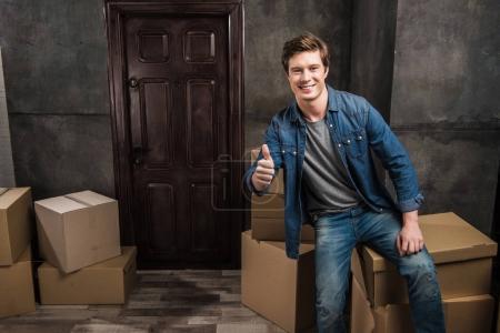 Photo pour Homme souriant assis sur une boîte en carton et montrant pouce vers le haut à la nouvelle maison - image libre de droit