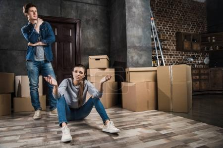Photo for Irritated woman sitting on floor while pensive man looking away at new home - Royalty Free Image