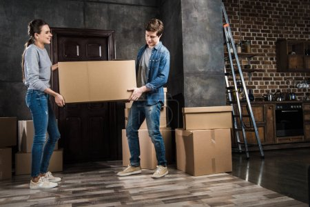 Photo for Side view of couple holding cardboard box together at new home, moving home concept - Royalty Free Image