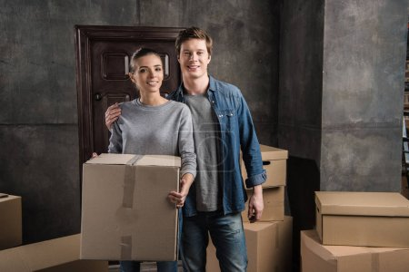 Photo for Portrait of man hugging girlfriend with cardboard box in hands at new home - Royalty Free Image