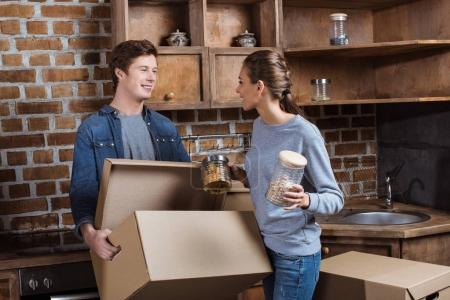 Photo for Happy couple unpacking cardboard box with stuff in kitchen at new home - Royalty Free Image