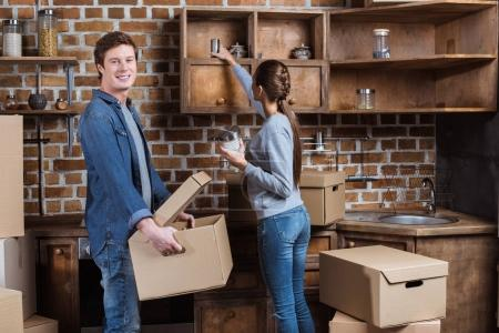 Photo for Man holding cardboard box while unpacking stuff together with girlfriend in kitchen at new home - Royalty Free Image