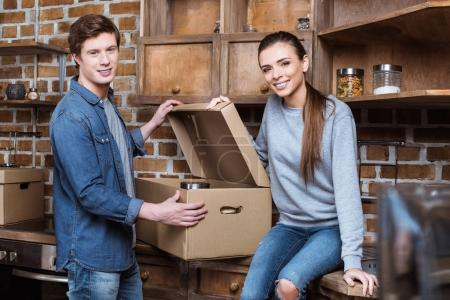 Photo for Smiling couple looking at camera while unpacking cardboard box with stuff in kitchen at new home - Royalty Free Image