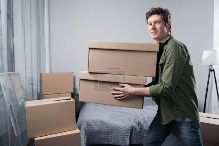 Photo for Side view of cheerful man with cardboard boxes in hands moving at new home - Royalty Free Image