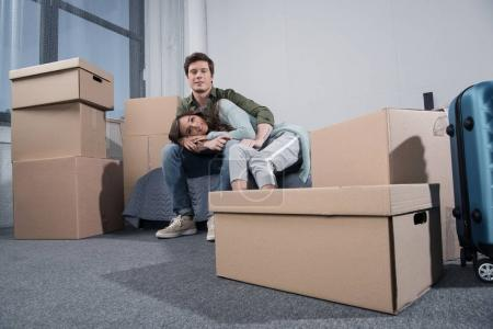 Photo for Couple sitting on bed in room full of cardboard boxes at new home - Royalty Free Image