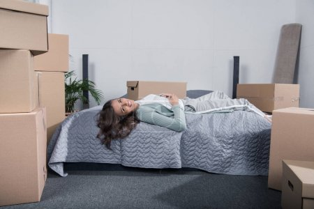 Photo for Tired woman lying on bed after unpacking cardboard boxes at new home, moving home concept - Royalty Free Image
