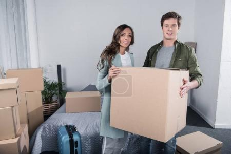 Photo for Portrait of couple looking at camera while carrying cardboard box at new home - Royalty Free Image