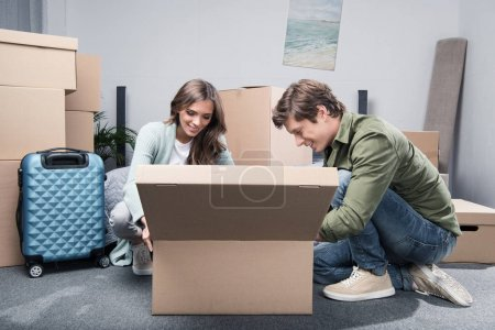 Photo for Smiling couple unpacking stuff from cardboard box together at new home - Royalty Free Image