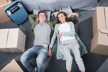 Foto de Vista aérea de joven pareja descansando en el piso en el dormitorio en casa nueva - Imagen libre de derechos