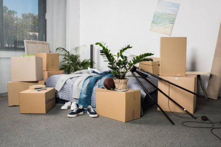 Photo for Room full of cardboard boxes and casual clothing on bed - Royalty Free Image