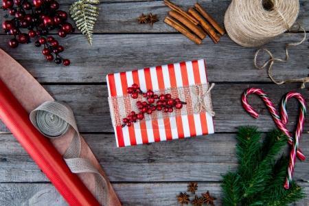 Foto de Vista superior de la Navidad presente con frutos rojos, bastones de caramelo y papel de embalaje sobre superficie de madera - Imagen libre de derechos