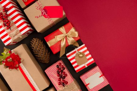 Photo for Top view of christmas gift boxes with pine cone and copy space on red - Royalty Free Image