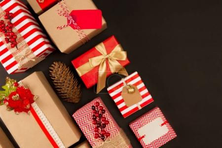 Photo for Top view of festive gift boxes and pine cone on black - Royalty Free Image
