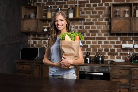 woman with paper bag full of food