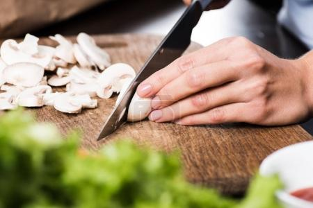 Photo for Partial view of woman cutting mushrooms while cooking dinner - Royalty Free Image