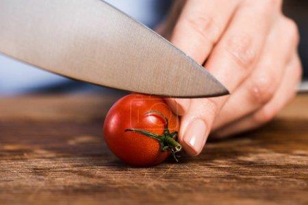 woman cutting cherry tomato