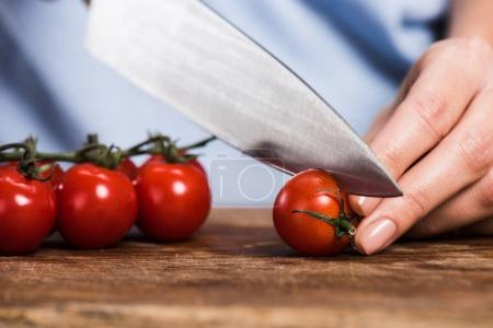 woman cutting cherry tomatoes