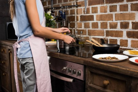 Photo for Cropped shot of woman preparing food in saucepan in kitchen at home - Royalty Free Image