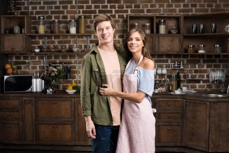 Photo pour Portrait de jeune couple souriant regardant la caméra tout en se tenant dans la cuisine à la maison - image libre de droit