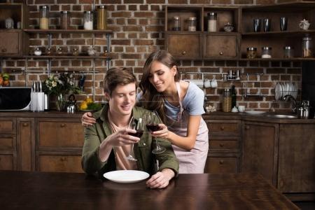 Photo pour Souriant couple sonnante verres sur le vin avant le dîner dans la cuisine à la maison - image libre de droit