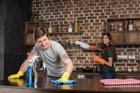 Photo pour Sourire jeune couple nettoyage cuisine ensemble à la maison - image libre de droit