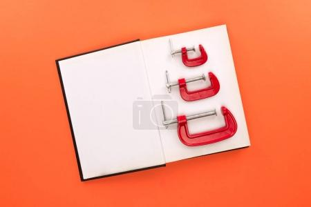 Open notebook and c-clamps