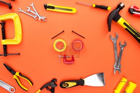 Photo for Top view shot of smiley face made of rolls of tape, screws and c-clamp, placed on orange surface with various reparement tools scattered around - Royalty Free Image
