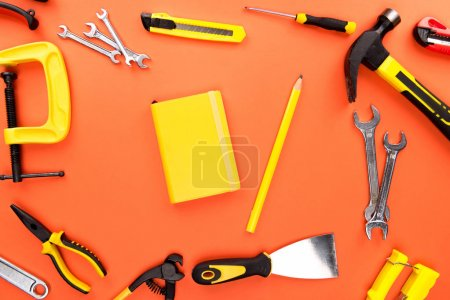 Photo for Top view shot of composition with yellow notebook and pencil, placed on orange surface with various reparement tools scattered around - Royalty Free Image