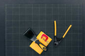 Notebook and carpentry tools on graph paper