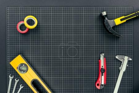 Photo for Top view shot of spirit level, tape, reparement tools and hardhats on graph paper background - Royalty Free Image