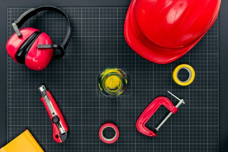 Photo for Top view shot of composition with various reparement tools, hardhat, ear muffs and flower in bottle on graph paper - Royalty Free Image
