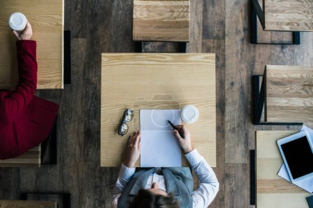 Businesswoman writing document in cafe