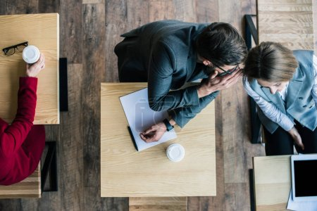 Photo for Top view of businesspeople gossiping in cafe while havin coffee - Royalty Free Image