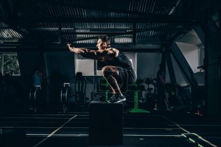 Photo for Fit sportsman exercising in gym, doing squats on a cube - Royalty Free Image