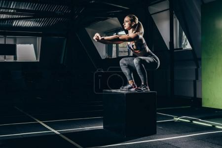 Photo for Fit sportswoman exercising in gym, doing squats on a cube - Royalty Free Image