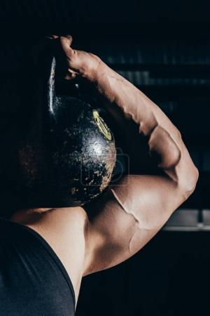 Photo for Cropped shot of athletic sportsman with embossed muscles holding a kettlebell on his shoulder - Royalty Free Image