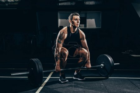 Photo for Athletic sportsman squatting before lifting a barbell with weights at gym - Royalty Free Image