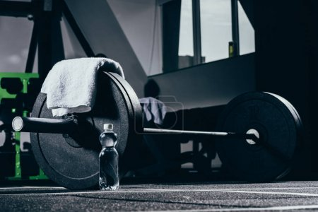 Photo for Barbell, towel and bottle of water on floor in gym - Royalty Free Image