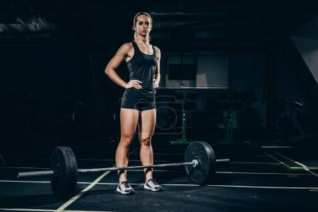 Photo for Young athletic sportswoman standing over a barbell placed on floor at gym - Royalty Free Image