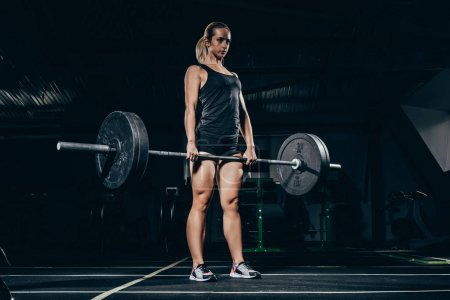 Photo for Young athletic sportswoman lifting a barbell with weights in gym - Royalty Free Image