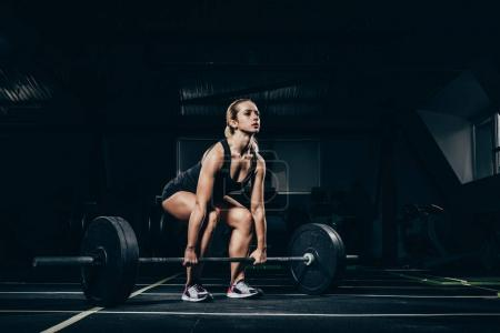 Photo for Young athletic sportswoman squatting while lifting a barbell with weights in gym - Royalty Free Image