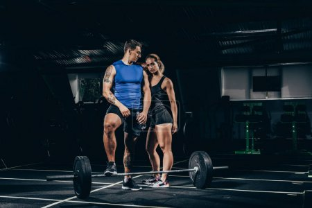 Photo for Fit sportsman and sportswoman in sportswear posing in gym with barbell placed on floor - Royalty Free Image