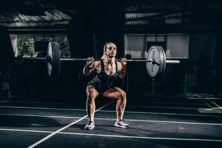 Photo for Young athletic sportswoman squatting while lifting a barbell in gym on her shoulders - Royalty Free Image