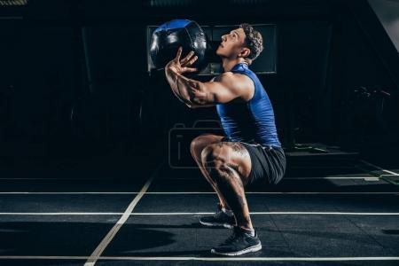 Photo for Young athletic sportsman squatting while exercising at gym with a weighted ball - Royalty Free Image